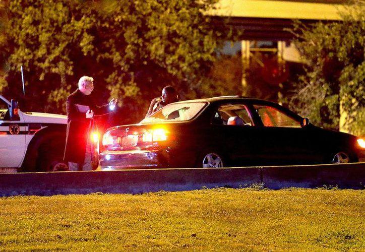 Un policía revisa un auto con una ventana echa trizas en el marco de un ataque con arma de fuego que segó dos vidas.  (Agencias)
