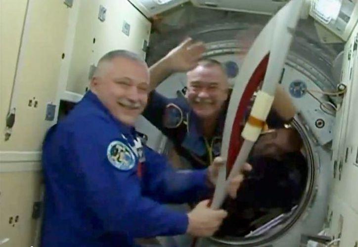 El cosmonauta Mijail Tyurin sostiene la antorcha olímpica de los Juegos Invernales de Sochi, antes de llevarla a bordo de un cohete Soyuz, hacia la Estación Espacial Internacional. (Agencias)