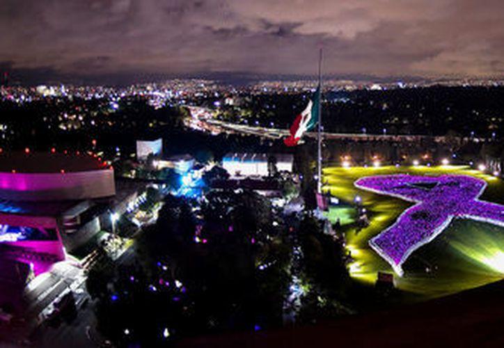 """Tras el grito en un altavoz de """"México está de pie"""", se encendió el relleno del lazo humano de miles de paraguas de color rosa. (Redacción/SIPSE)"""