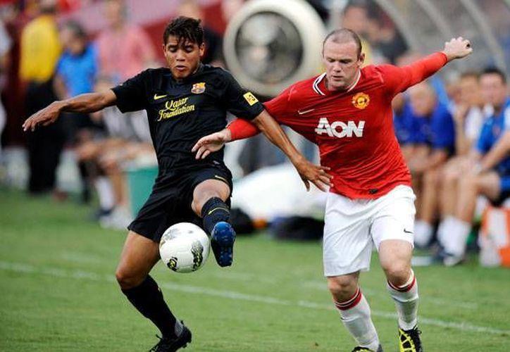 Jonathan dos Santos (i) disputa el balón contra Wayne Rooney, del Manchester United. (starmedia.com/Archivo)
