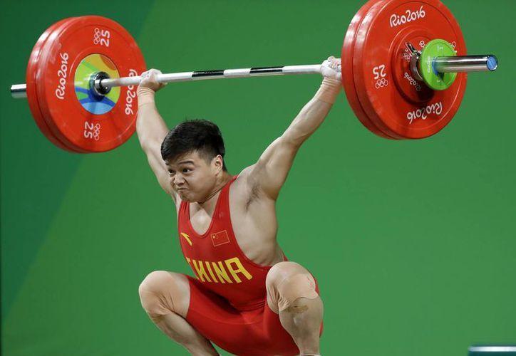 El deportista chino Qingquan Long ganó la medalla de oro al cargar 307 kilos. (AP /Mike Groll)