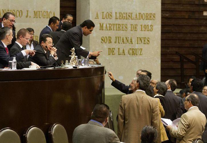Los legisladores del PRD, Movimiento Ciudadano y el PT tomaron la tribuna de la Cámara por unos momentos. (Notimex)