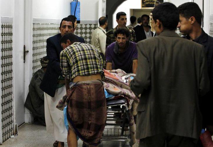 Varios hombres ayudan a una víctima del doble atentado perpetrado en una mezquita de Saná, Yemen, en el cual resultaron muertas unas 28 personas. (EFE)