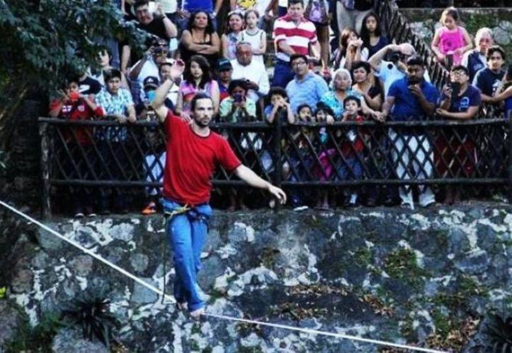 El acróbata australiano Christian Waldner atraviesa la cuerda floja sobre el cenote Zací de Valladolid. (Milenio Novedades)