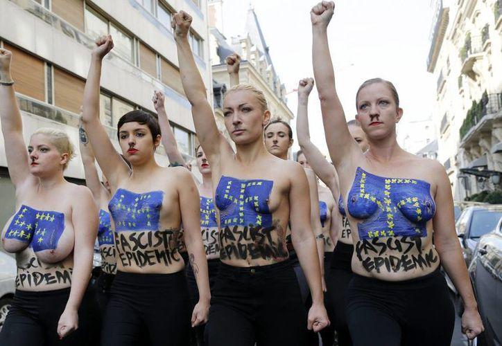 """Imagen de archivo que muestra a activistas del grupo ucraniano Femen protestando con sus cuerpos pintados en los que se lee """"Epidemia fascista"""", frente a la Maison des Centraliens. (EFE/Archivo)"""