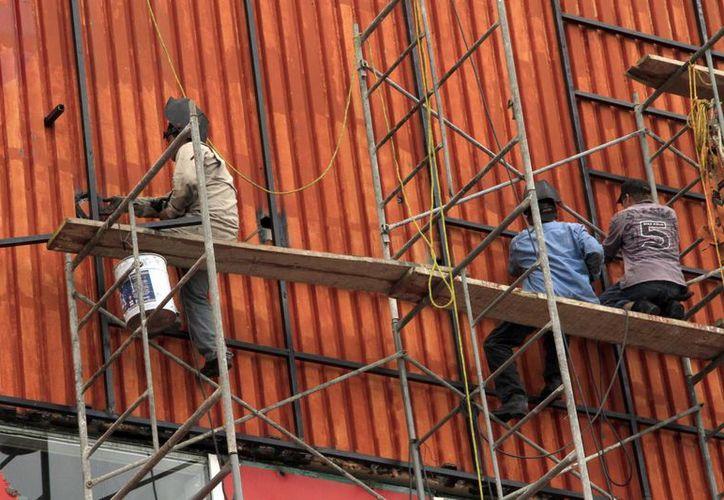 Del número de fallecidos por accidentes laborales, seis corresponden al ramo de la construcción y uno, al de la industria. Imagen de un grupo de empleados laborando desde las alturas. (Milenio Novedades)