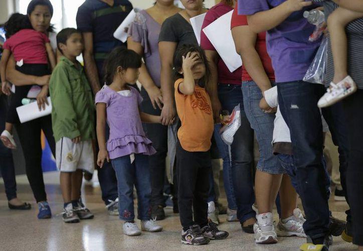 Inmigrantes que entraron de forma ilegal a Estados Unidos esperan en fila por sus boletos en una estación de autobús tras salir de las instalaciones de la agencia de protección de fronteras y aduanas en McAllen, Texas. (Agencias)