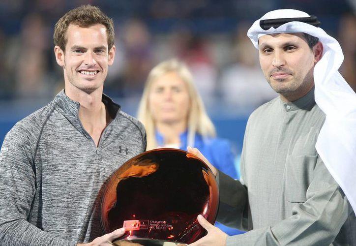 El tenista británico Andy Murray (i) posa con el trofeo de campeón del torneo de exhibición de Abu Dabi junto a Khaldoon Al Mubarak, del departamento del CEO Mubadala. (EFE/EPA)