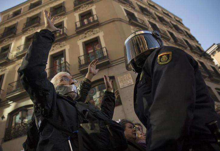 Policías tratan de acordonar una zona de protestas en Madrid, en el marco de la propuesta de una ley para frenar las manifestaciones públicas. (Foto: AP)