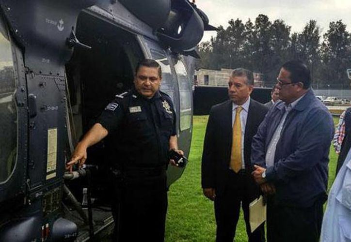 Imagen del personal de la Comisión Nacional de los Derechos Humanos durante la inspección del helicóptero que participó en el enfrentamiento en Tanhuato. (@CNDH)
