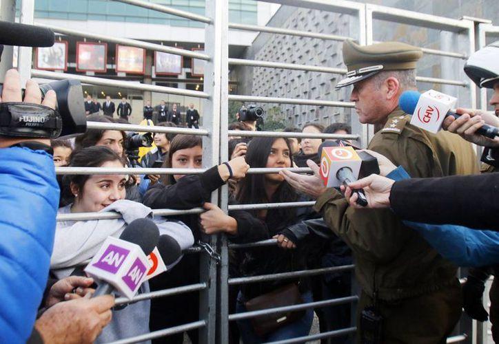 Un integrante de la policía chilena habla con estudiantes durante una toma que realizaron al edificio del canal de Televisión Nacional de Chile (TVN) hoy, en Santiago de Chile, Chile. (EFE)