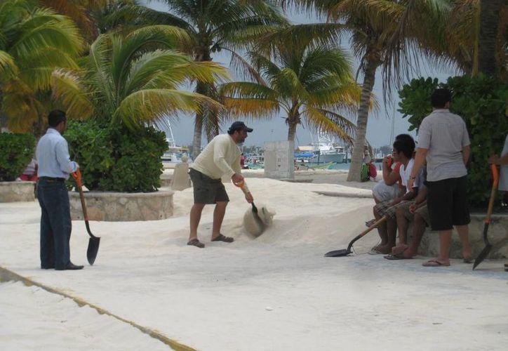 Con palas y carretillas se retiró la arena de la avenida. (Lanrry Parra/SIPSE)