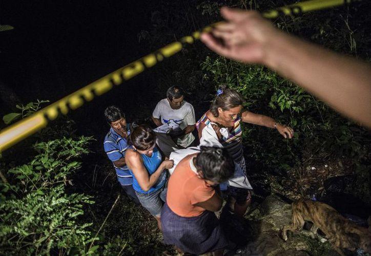 Parientes de un pandillero de la Mara Salvatrucha recuperan su cuerpo de una zanja después de que el hombre muriera abatido por la policía en un tiroteo en Olocuilta, El Salvador. (Agencias)