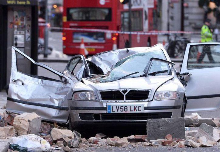 Escombros sobre un vehículo destrozado tras caer un cornisa de un edificio, como consecuencia de los fuertes vientos. (EFE)