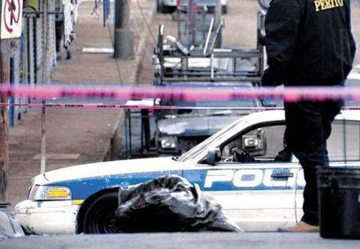 Policías resguardan el cuerpo abandonado por los satánicos. (Milenio Digital)