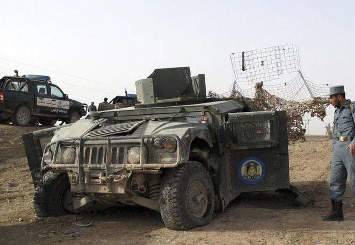 Policías afganos inspeccionan el escenario de la explosión de una bomba en Shindig Mandan. (EFE)