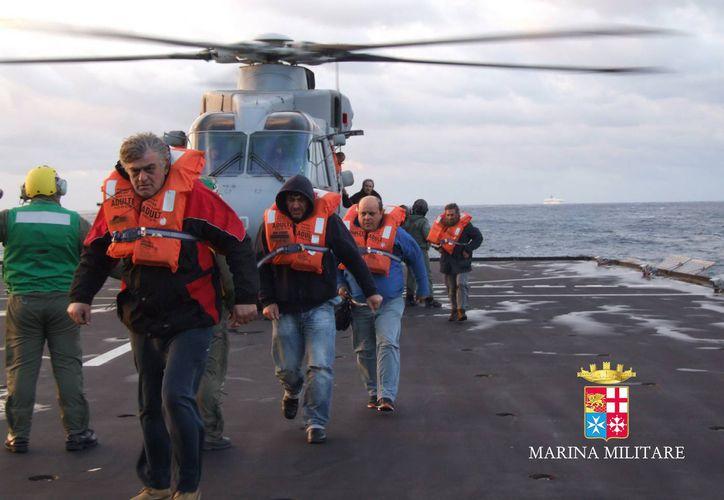 Imagen proporcionada por la marina italiana, pasajeros y tripulantes del barco de bandera italiana Norman Atlantic, incendiado en el mar Adriático, son rescatados del buque de la marina italiana San Giorgio. (AP/Italian Navy, ho)