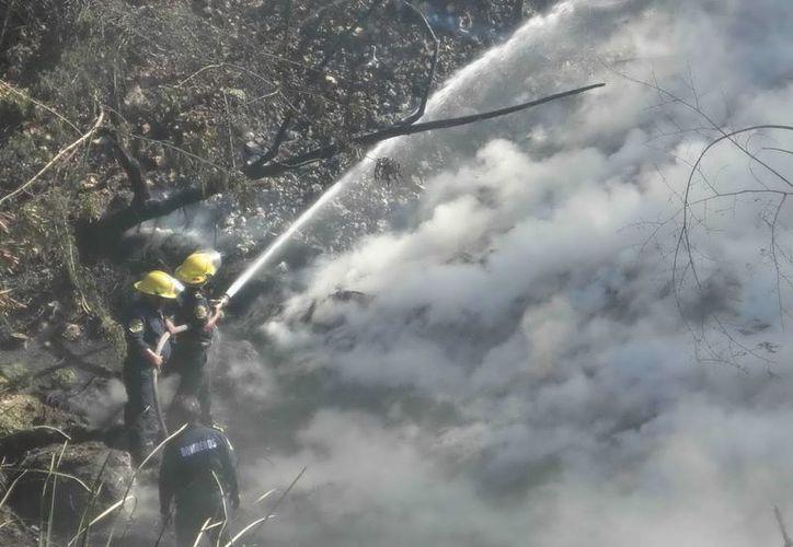 El fuego consumió cientos de llantas en el fondo del barranco. (SIPSE)