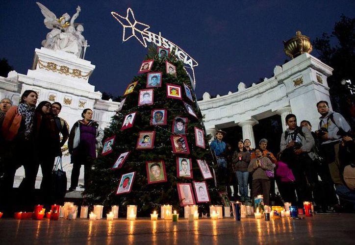 Asociaciones civiles 'plantaron' un árbol navideño en el que colocaron las fotos de los 43 estudiantes desaparecidos de Ayotzinapa, como una forma de protestas por la falta de avance en las investigaciones. La imagen es de contexto. (AP)