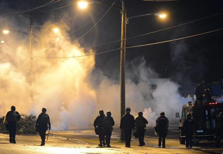 Agentes de Policía ante manifestantes que desobedecieron el toque de queda de medianoche y se reunieron en West Florissant Avenue en Ferguson, Missouri (EFE).