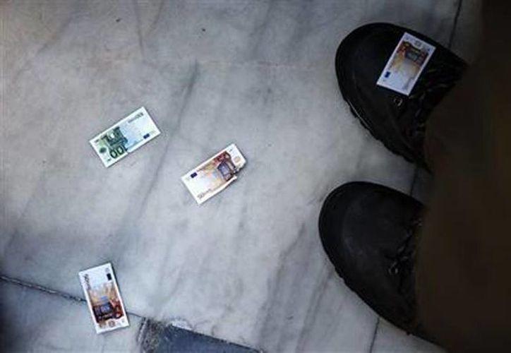 Manifestantes en favor del euro arrojan billetes falsos durante una protesta en el exterior del Parlamento griego, en Atenas, el 22 de mayo de 2015. (Foto AP/Daniel Ochoa de Olza)