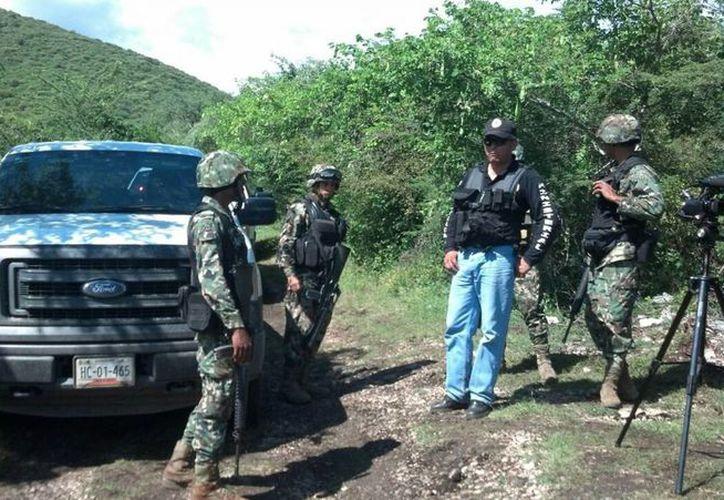 Elementos del Ejército y Policía Ministeriol vigilan el acceso al lugar donde se encontraronn restos óseos en fosas clandestinas en el punto conocido como Pueblo Viejo, en Iguala, Guerrero. (Archivo/Notimex)