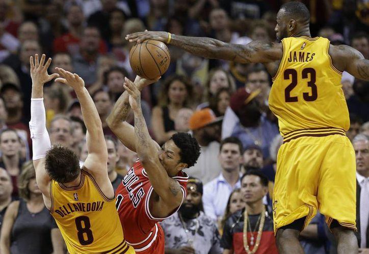 LeBron James (23), de Cavs, bloquea un disparo de Derrick Rose (1), guardia de Bulls de Chicago mientras su compañero Matthew Dellavedova (8) intenta defender en el quinto partido de la serie, que está 3-2 a favor de Cleveland. (Foto: AP)