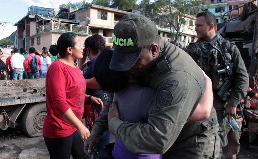 Un policía que sobrevivió al ataque, atribuido a las FARC, en Inza, se abraza efusivamente con un familiar. El Gobierno dijo que 9 personas murieron y varios policías y militares resultaron heridos. (Agencias)