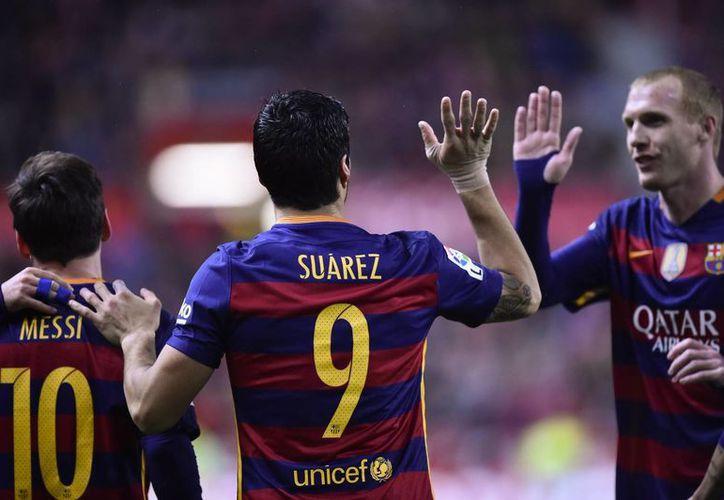 El Barcelona venció al Sporting de Gijón 3-1 con goles de Lionel Messi (2) y Luis Suárez. (Imágenes de AP)