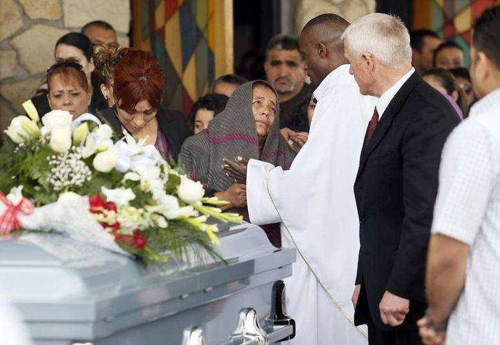 El padre Lutakome Nsubuga consuela a Agapita Montes Rivera, madre de Antonio Zambrano Montes que fue muerto a manos de policias estadounidenses de Pasco. (Agencias)