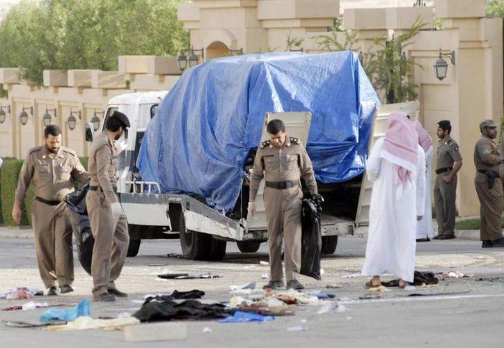 Policías inspeccionan el lugar donde se produjo un tiroteo con opositores en Arabia Saudí. (EFE)