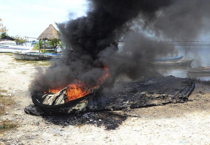 Los hombres de mar presentarán una denuncia ante las autoridades. Imagen del momento del incendio de una de las lanchas de pescadores campechanos. (Milenio Novedades)