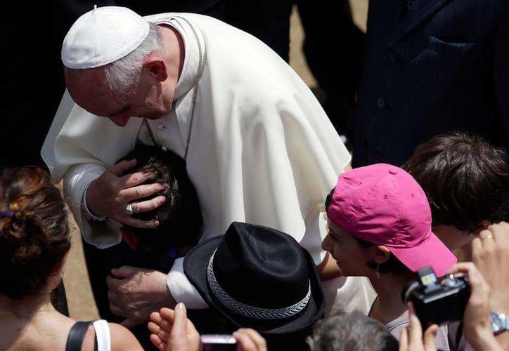 El papa besa a un niño después de dirigir el rezo del Angelus en Castel Gandolfo, este domingo. (AP)