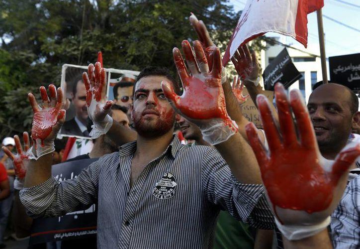 Partidarios del régimen pro-sirio libanés protestan contra un posible ataque a Siria cerca de la embajada de EU. (Agencias)