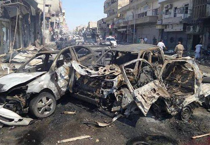 Imagen de dos coches que fueron quemados después del ataque aéreo del gobierno sirio en la ciudad nororiental de Raqqa, Siria. (Agencias)