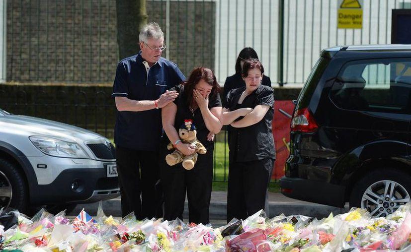 Lyn Rigby, madre del soldado fallecido  Lee Rigby, con otros familiares y junto a mensajes de apoyo. (Agencias)