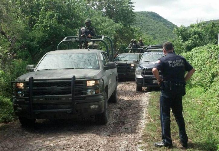Elementos del Ejército y Policía Ministeriol vigilan el acceso al lugar donde se encontraronn restos óseos en fosas clandestinas en el punto conocido como Pueblo Viejo, en Iguala, Guerrero. (Notimex)