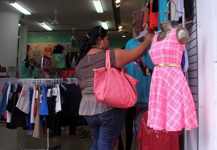 """Una mujer escoge entre varias prendas previo al  """"Día de la Madre"""", en el Centro. (Milenio Novedades)"""