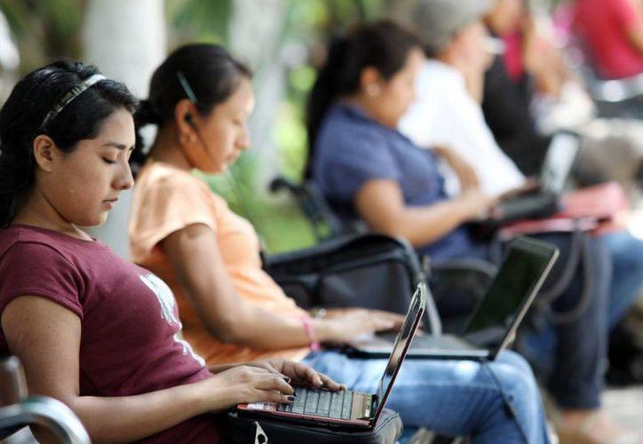 Los jóvenes son los que más optan  por trabajar por su cuenta como 'freelance'. Imagen de unas estudiantes que navegan en internet en un parque de Mérida.  (Milenio Novedades)