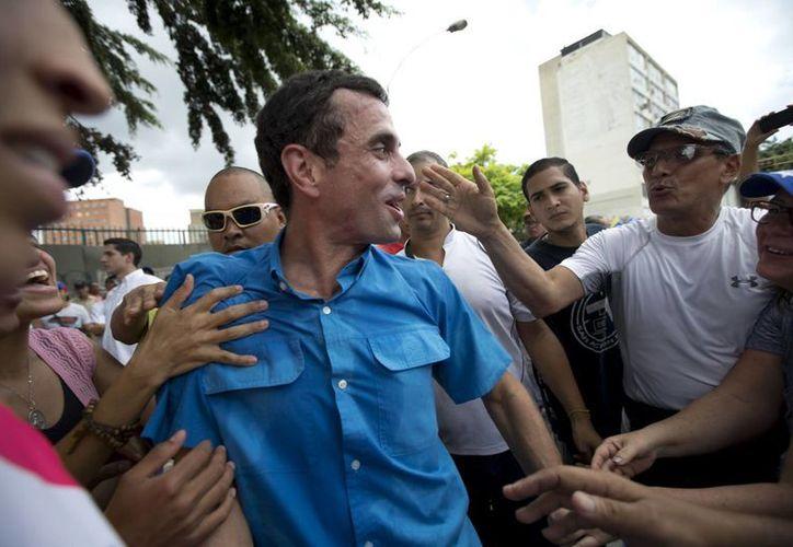 El líder opositor Henrique Capriles, centro, es recibido por sus seguidores durante una marcha de la oposición en Caracas, Venezuela, el pasado sábado. Manifestantes exigen que  funcionarios electorales aceleran la certificación de las firmas de la petición para el retiro del presidente Nicolas Maduro. (Foto AP / Ariana Cubillos)