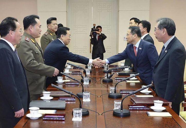 Fotografía facilitada por el Ministerio surcoreano de Unificación que muestra al jefe de la delegación surcoreana, Kim Kyou-hyun (2ºdcha), estrechando la mano de su homólogo norcoreano, Won Dong-yeon (3ºdcha), en Panmunjom, Corea del Sur. (EFE)