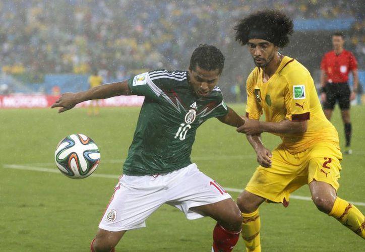 Giovanni (i) se quita la marca de Benoit Assou-Ekotto. El mexicano anotó ante Camerún dos veces, pero le anularon sus goles por supuestos fuera de lugar. (Foto: AP)