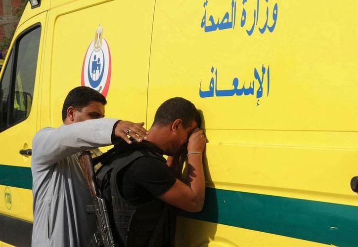 Un integrante de la fuerza de Seguridad llora tras conocer la noticia de que 4 de sus compañeros murieron en un ataque de enmascarados a un sitio cercano a una pirámides. (AP)