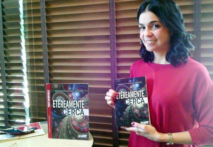 La escritora Arminda Villanueva Garrido al mostrar un ejemplar de su libro 'Etéreamente cerca'. (Milenio Novedades)