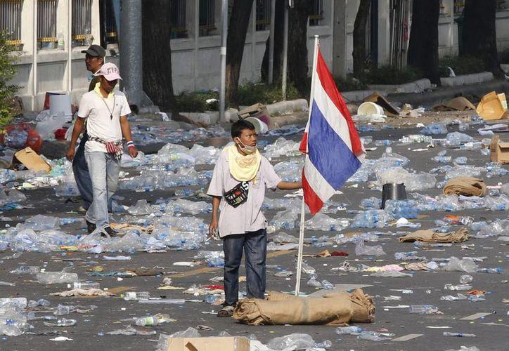 Un manifestante sujeta una bandera nacional para celebrar la entrada en la sede de la Policía Metropolitana en Bangkok. (EFE)