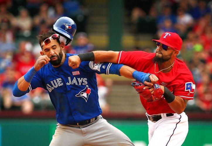 José Bautista (izquierda) de los Azulejos de Toronto, recibe un golpe en el rostro de parte del segunda base venezolano Rougned Odor, de los Rangers de Texas. Este último fue sancionado con ocho partidos. (AP)