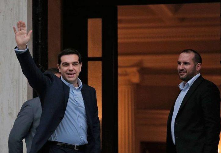 Alexis Tsipras saluda con la mano en alto a los asistentes que se encuentran afuera del la Mansión Maximo, en Atenas, donde juramentó como Primer Ministro de Grecia.  (AP)