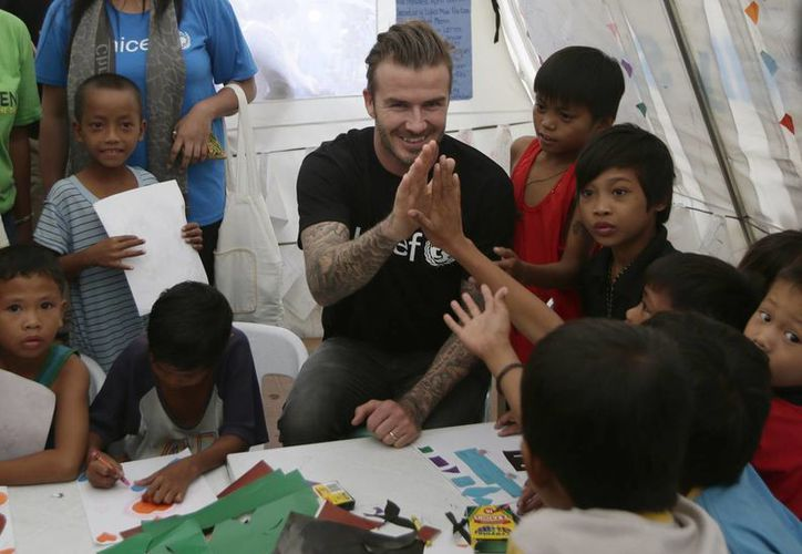 Davida Beckham fue recibido por cientos de damnificados que han estado viviendo en tiendas de campaña suministradas por la ONU en las afueras de un estadio. (Agencias)