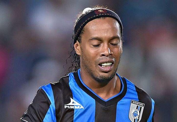 Ronaldinho (foto) adelantó que el próximo mes de julio estará en México para despedirse personalmente de los aficionados de los Gallos blancos del Querétaro. En la foto, Dinho se lamenta, tras concluir el partido de la final del Clausura 2015. (AP)