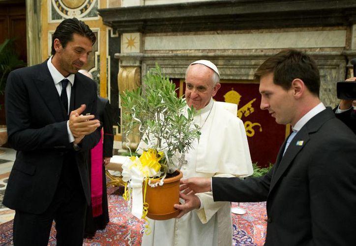 Varios jugadores le entregaron al Papa camisas y balones personalizados, pero Messi prefirió darle una planta. (Agencias)
